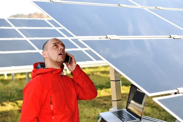 Ingenieur, der mit laptop durch sonnenkollektoren, sprechend am handy arbeitet
