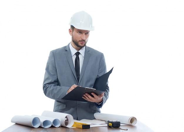 Ingenieur, der nachdenklich beim schreiben auf sein klemmbrett schaut.