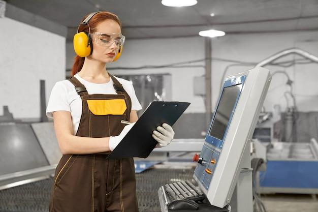 Ingenieur, der ordner hält und computergesteuerte maschine bedient.