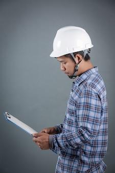 Ingenieur, der pläne hält und anmerkungen über klemmbrett bei der stellung auf grauem hintergrund liest.