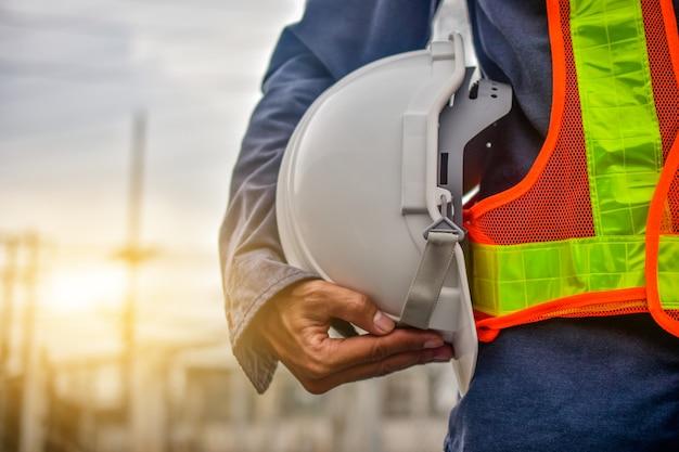 Ingenieur, der schutzhelmbauarbeiterberufssicherheitsarbeitsindustriegebäude-personenmanagerservice hält