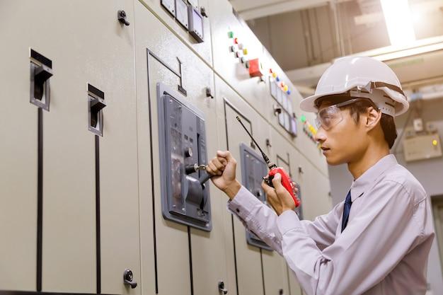 Ingenieur, der vor dem bedienfeld im kontrollraum steht.