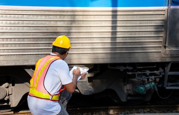 Ingenieur, der zug auf wartung in der station überprüft
