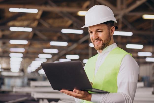 Ingenieur des jungen mannes, der an fabrik arbeitet