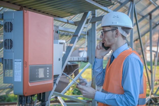 Ingenieur, ein mann in uniform, überprüft das steuerungssystem der solarstation auf dem hintergrund von sonnenkollektoren.