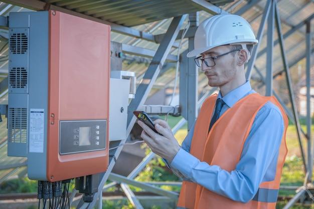 Ingenieur, ein mann in uniform, überprüft das steuerungssystem der solarstation auf den sonnenkollektoren.