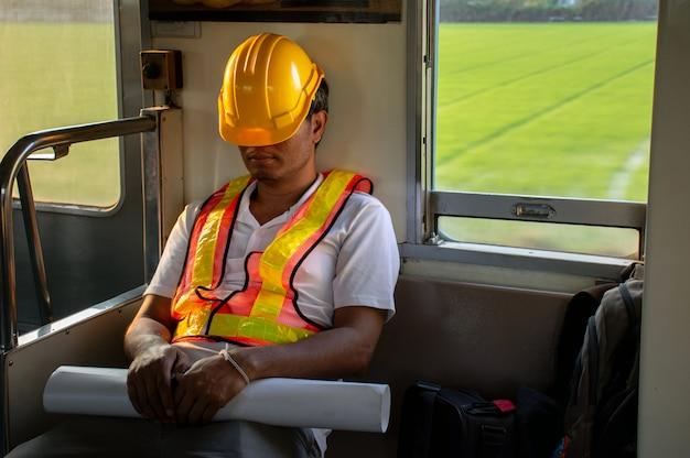 Ingenieur ermüdet während der arbeitsstunden im zug einschlafen
