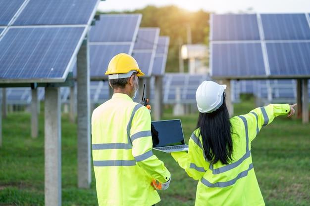 Ingenieur frau hält digital tablet arbeitstechniker in sonnenkollektoren.
