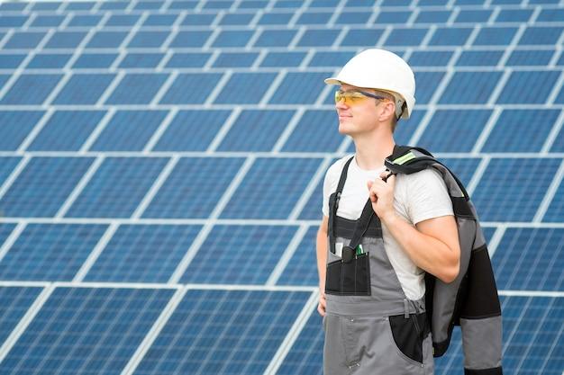 Ingenieur für sonnenkollektoren in weißem fass, gelber schutzbrille und grauem outfit in der nähe des feldes für sonnenkollektoren. alternative energiearten. konzept der erneuerbaren energien, technologie. mann bei der arbeit..