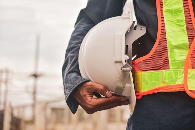 Ingenieur hält weißen helm sicherheit schutzhelm kopie spec