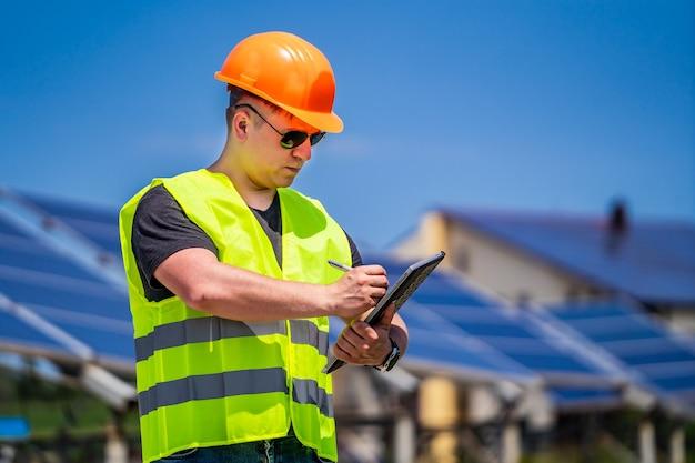 Ingenieur im arbeiterhelm auf sonnenkollektorenhintergrund. solarenergie-panel. grüne energie. elektrizität. power-energie-panels.