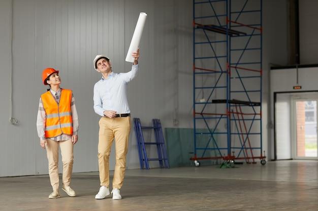 Ingenieur im arbeitshelm, der auf etwas zeigt und dem arbeiter, der in einem leeren gebäude steht, den arbeitsprozess erklärt