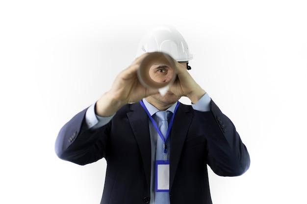 Ingenieur im schutzhelm, der kamera durch blaupause betrachtet, die in rolle gedreht wird