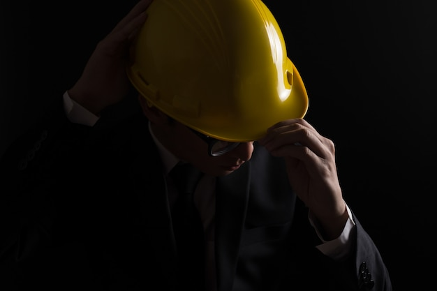 Ingenieur im schwarzen anzug auf lokalisiertem schwarzem hintergrund