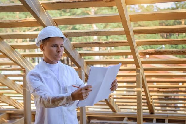 Ingenieur im weißen helm prüft dachrahmen