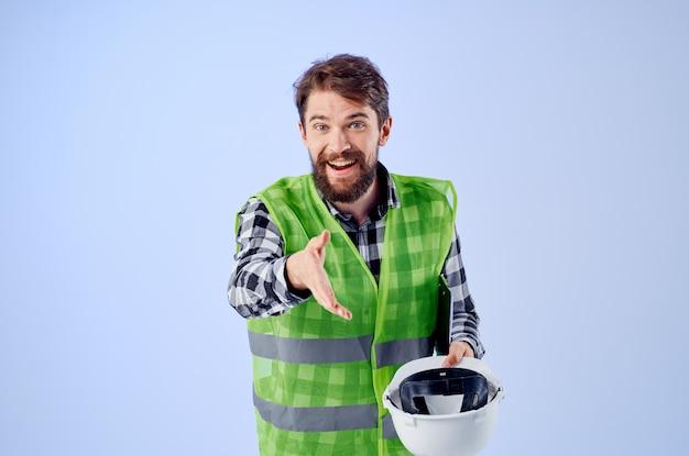 Ingenieur in einem grünen vestconstruction arbeitsdesign blauem hintergrund