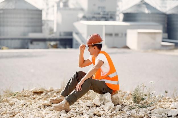 Ingenieur in einem helm, der von der fabrik sitzt