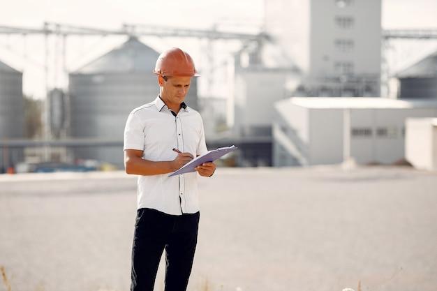 Ingenieur in einem helm, der zur fabrik steht
