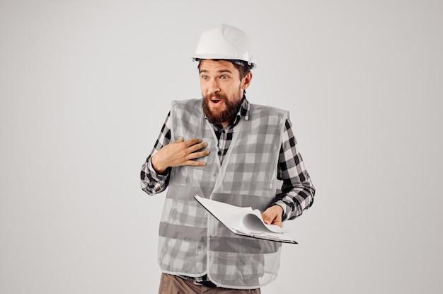 Ingenieur in einem weißen helm blaupausen professioneller isolierter hintergrund