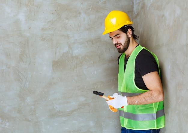 Ingenieur in gelbem helm und industriehandschuhen mit einer metallischen axt
