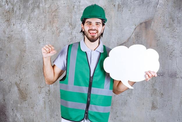 Ingenieur in gelber ausrüstung und helm, der eine infotafel in wolkenform hält und seine faust zeigt