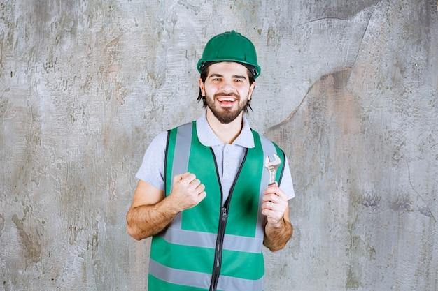 Ingenieur in gelber ausrüstung und helm, der einen metallischen schraubenschlüssel hält und ein positives handzeichen zeigt.