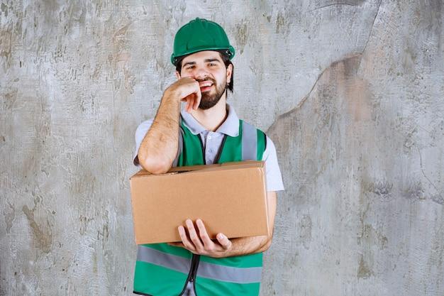 Ingenieur in gelber ausrüstung und helm mit einem karton und sieht verwirrt und nachdenklich aus.