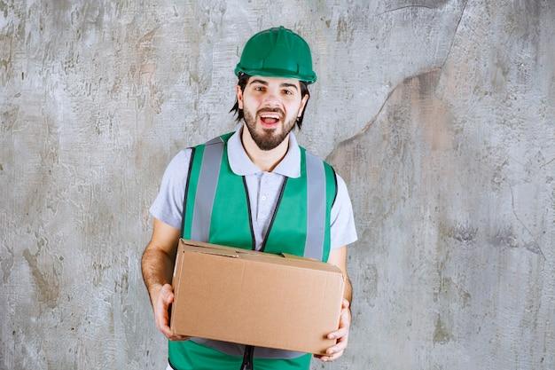 Ingenieur in gelber ausrüstung und helm mit einem karton.