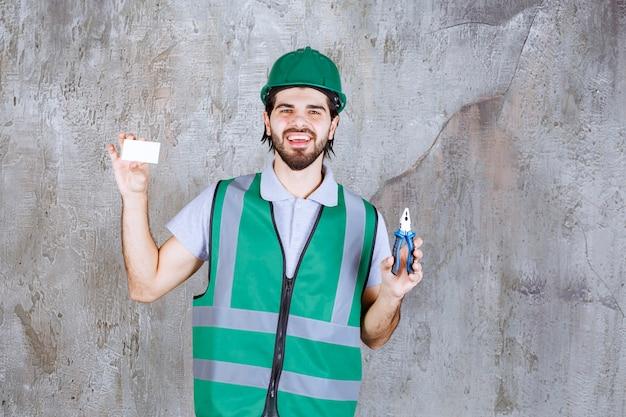 Ingenieur in gelber ausrüstung und helm mit zange und präsentiert seine visitenkarte