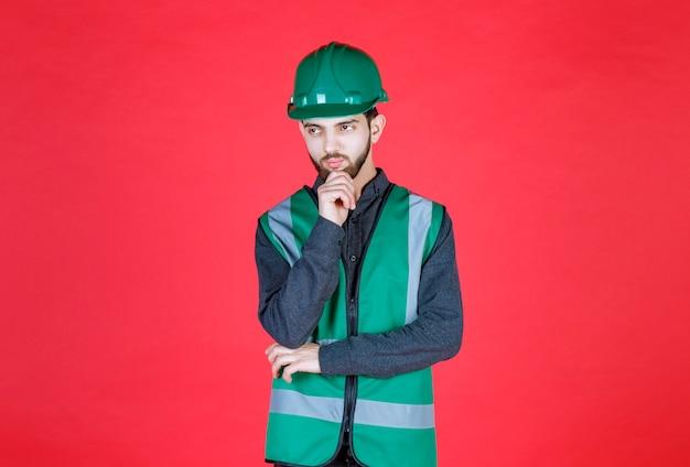 Ingenieur in grüner uniform und helm denken und planen.