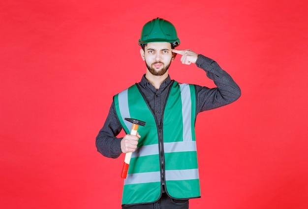 Ingenieur in grüner uniform und helm, der eine holzaxt hält und denkt.