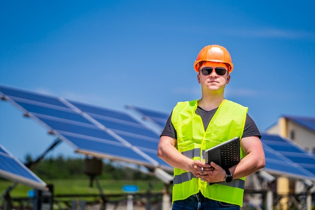 Ingenieur in sonnenbrille und helm auf dem hintergrund eines solarkraftwerks.