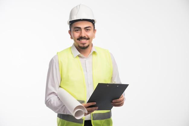Ingenieur in uniform, der die aufgabenliste überprüft und lächelt.
