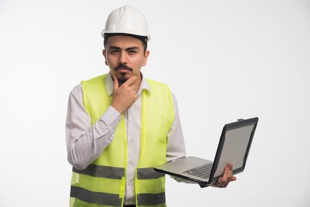 Ingenieur in uniform hält einen laptop und denkt nach.