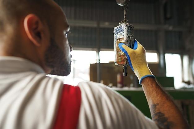 Ingenieur in uniform mit von der decke hängender kransteuerung in einer fabrik