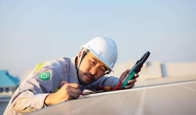Ingenieur inspiziert sonnenkollektoren auf dem dach eines modernen hauses. alternatives energieökologisches konzept.