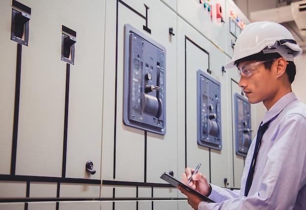 Ingenieur ist spannung oder strom durch voltmeter im bedienfeld des kraftwerks überprüfen.