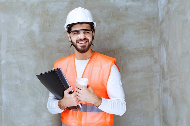 Ingenieur mann im weißen helm, der eine schwarze mappe und eine tasse getränk hält.