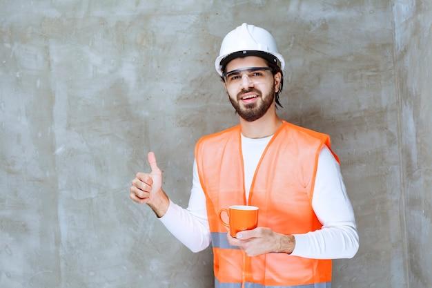 Ingenieur mann im weißen helm hält einen orangefarbenen becher und genießt den geschmack des getränks.