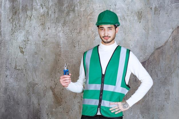Ingenieur mann in gelber uniform und helm hält blaue zange zur reparatur.