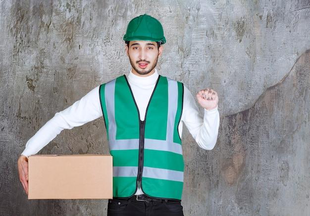 Ingenieur mann in gelber uniform und helm hält ein papppaket und zeigt seine faust.
