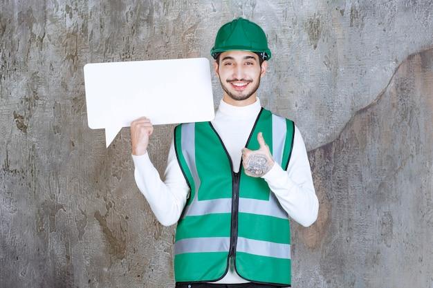 Ingenieur mann in gelber uniform und helm hält eine leere infotafel und zeigt positives handzeichen.