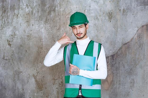 Ingenieur mann in gelber uniform und helm hält einen blauen ordner und bittet um einen anruf.