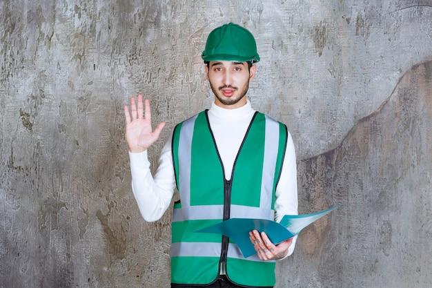 Ingenieur mann in gelber uniform und helm hält einen blauen ordner und stoppt etwas.