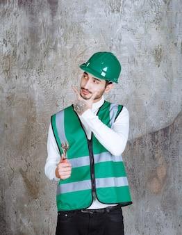 Ingenieur mann in gelber uniform und helm hält einen metallschlüssel zur reparatur und sieht nachdenklich aus.