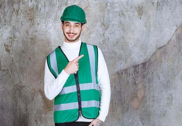 Ingenieur mann in gelber uniform und helm mit der rechten seite.
