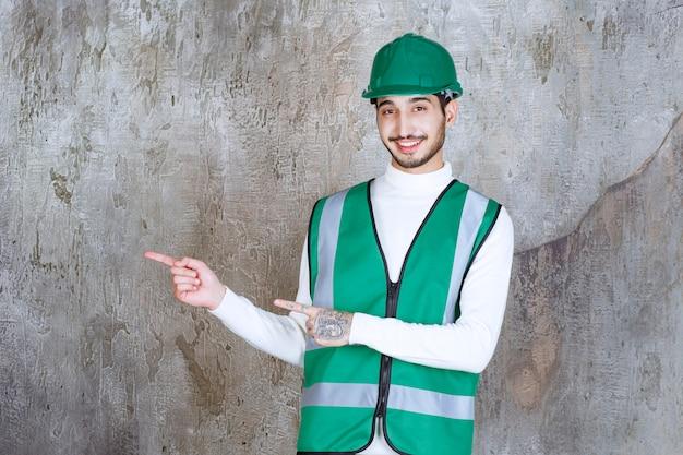 Ingenieur mann in gelber uniform und helm zeigt die linke seite