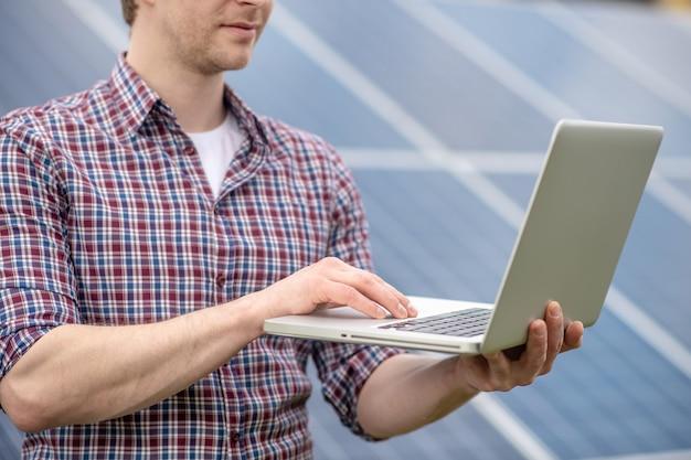 Ingenieur. mann in kariertem hemd, der an einem laptop arbeitet, der draußen vor dem hintergrund eines grauen solarpanels steht, der untere teil des gesichts ist sichtbar