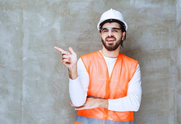 Ingenieur mann in weißem helm und schutzbrille zeigt auf seinen kollegen oder auf etwas beiseite.