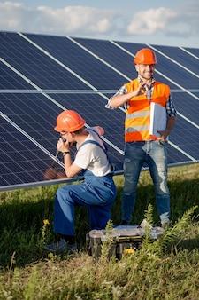 Ingenieur mit dem bohrgerät, das sonnenenergieplatten installiert.